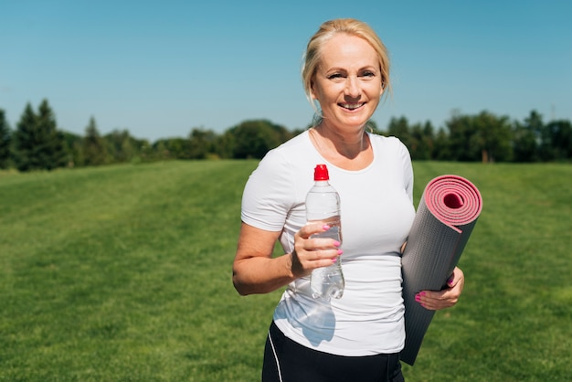 Smiley woman with yoga mat and water bottle