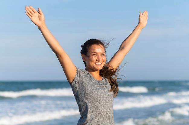 ビーチで運動するスマイリー女性