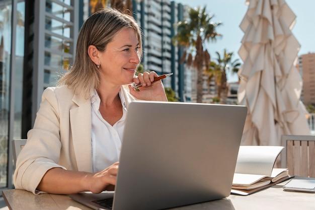 Smiley woman working at table medium shot