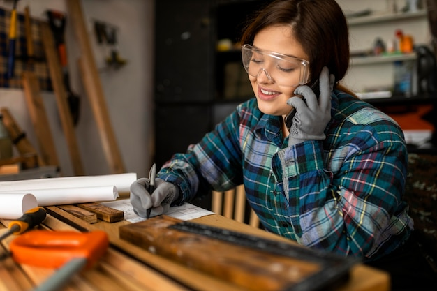 Smiley woman in workshop talking on phone