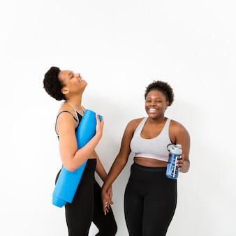 Улыбающиеся женщины в спортзале на перерыве
