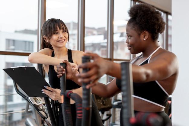 Улыбающиеся женщины в спортзале разговаривают друг с другом
