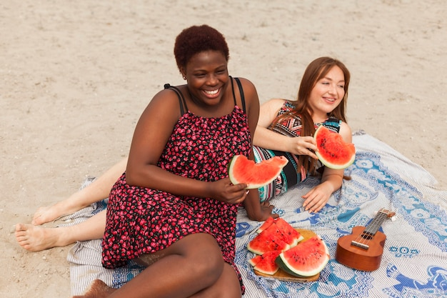 Smiley women on the beach eating watermelon
