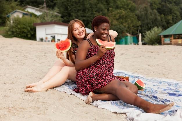 Smiley women at the beach enjoying watermelon