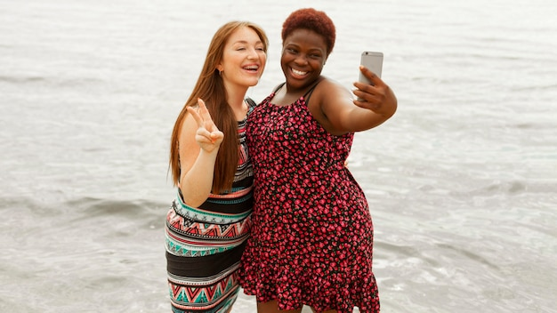 Smiley women at the beach taking selfie