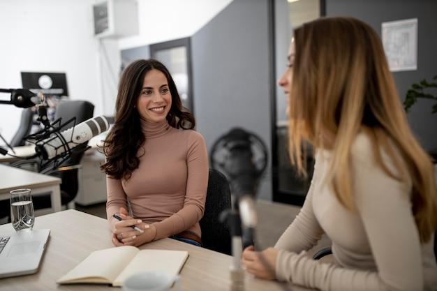 Смайлик женщины вместе вещают по радио