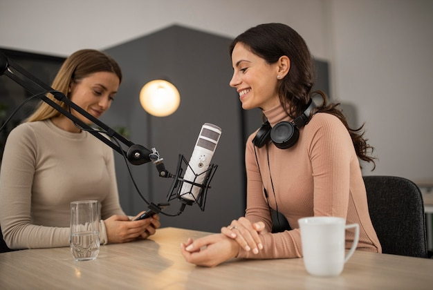 Smiley women doing a podcast on radio with a microphone