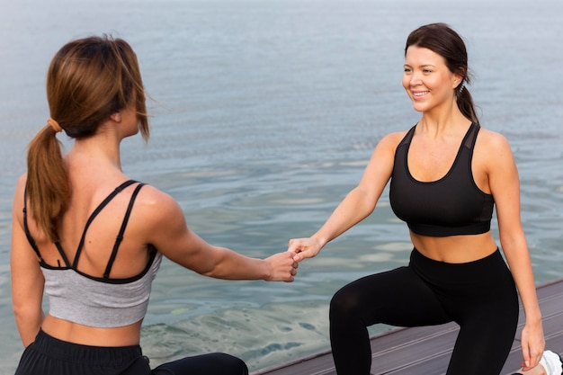 Smiley women exercising together outdoors