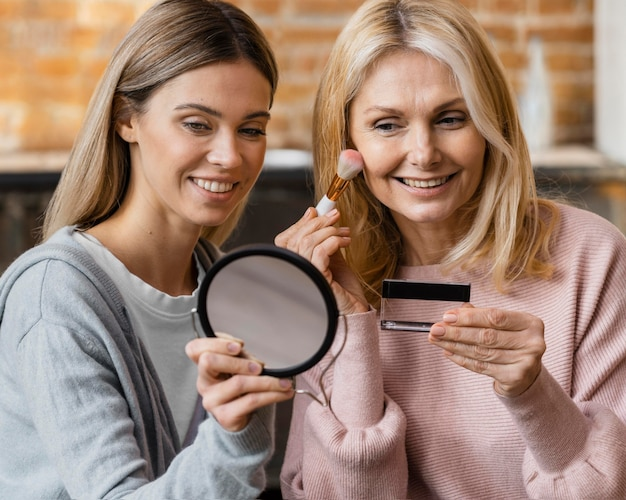 Smiley women getting their make-up on at home