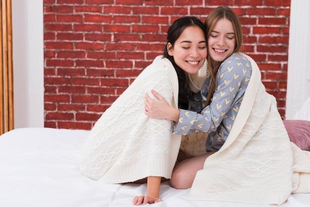 Smiley women hugging and sharing blanket