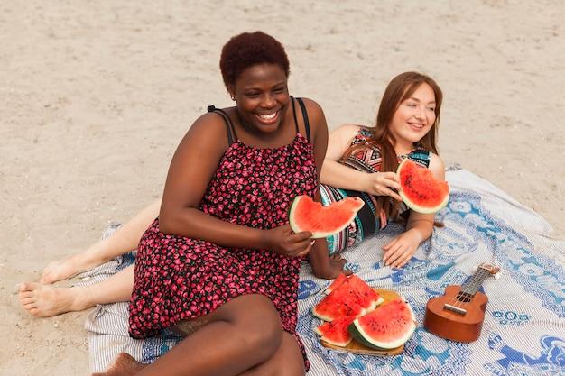 Улыбающиеся женщины на пляже едят арбуз