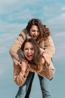 Смайлик женщины вместе позируют на открытом воздухе