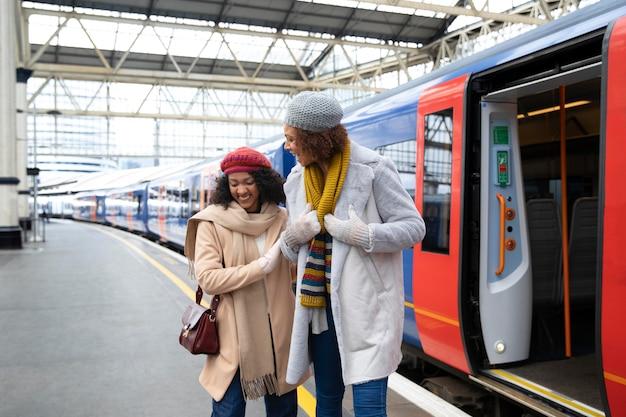 Smiley women at train station medium shot