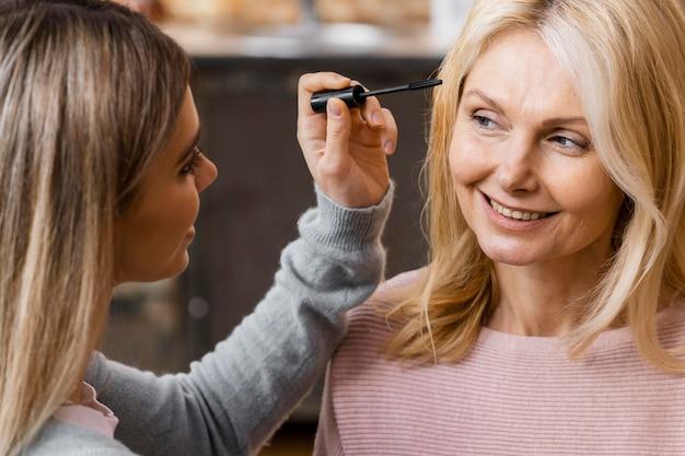 Donne di smiley che usano il mascara a casa