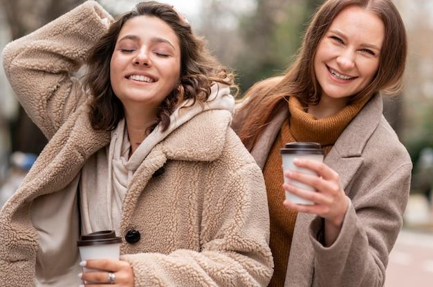 屋外でコーヒーカップを持つスマイリー女性