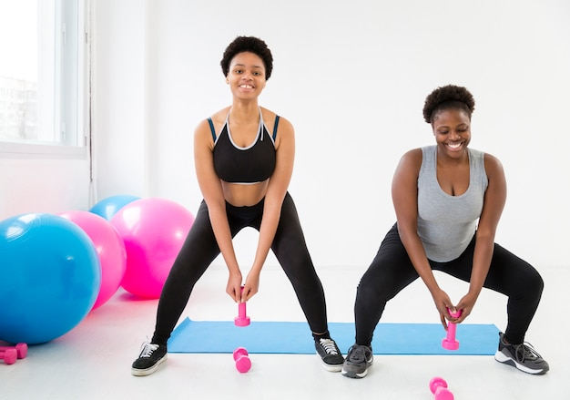 Smiley women working with weights