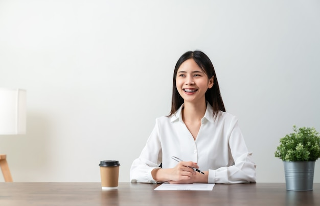 Smiley young asian woman sitting at a wooden table with holding pen and document information on the desk