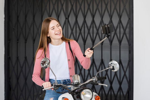 Smiley young blogger recording herself  sitting on her motorbike