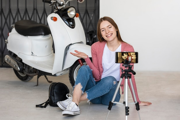 Smiley young blogger recording herself  sitting next to her motorbike
