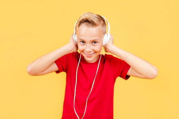 Smiley young boy listening music