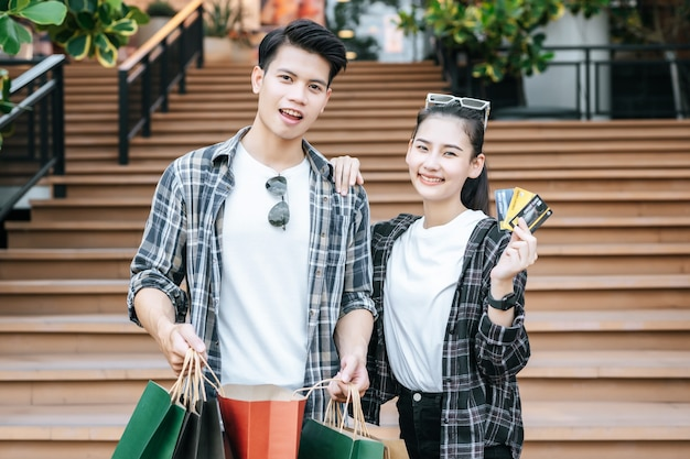 Smiley young couple holding multiple paper shopping bag