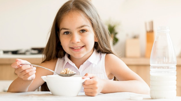 Smiley young girl eating cereals for breakfast