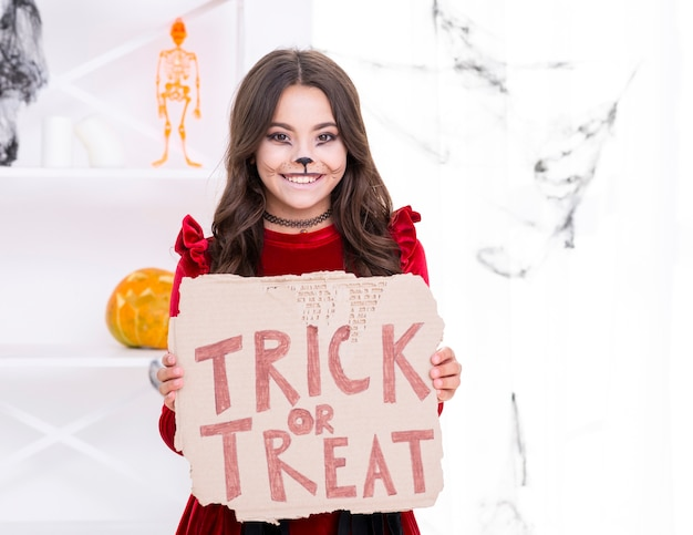 Smiley young girl holding trick or treat sign