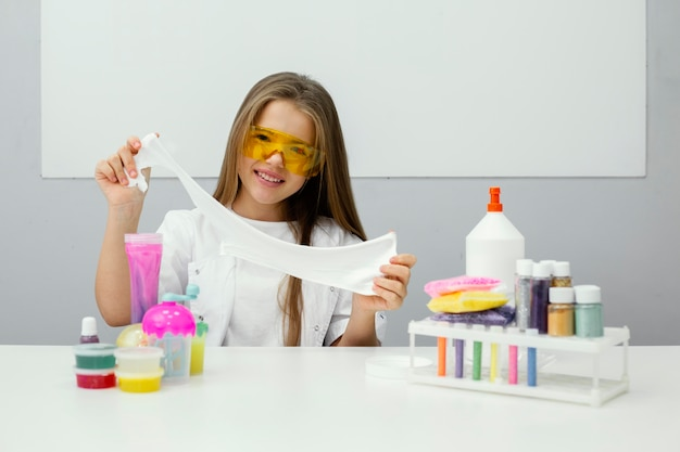 Smiley young girl scientist experimenting with slime