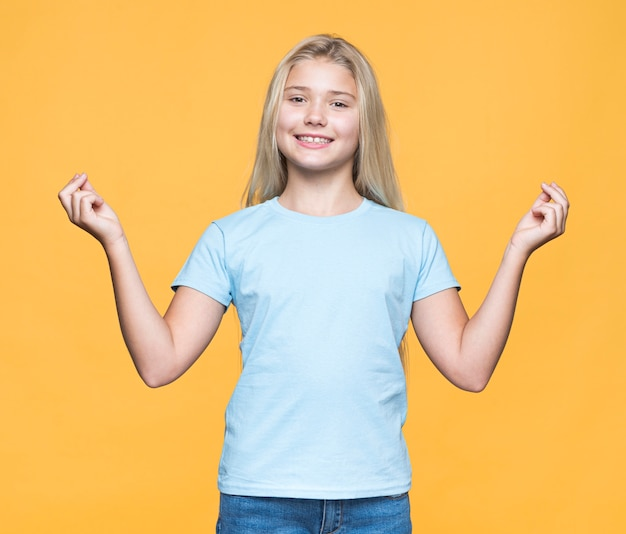Smiley young girl with yellow background