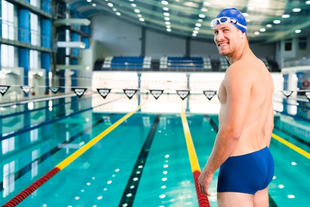 Smiley young male swimmer at pool