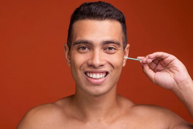 Giovane maschio di smiley utilizzando i bastoncini per le orecchie