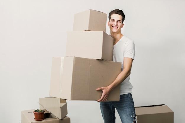 Smiley young man holding carton boxes