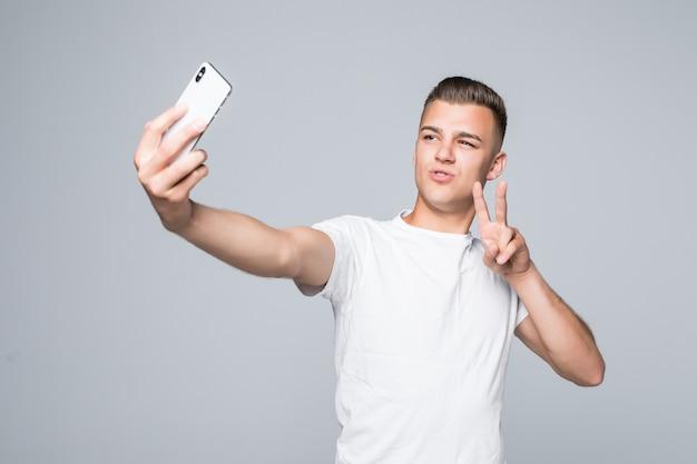 スマイリーの若い男は白いtシャツを着て、銀色のスマートフォンで自分撮りの勝利のサインを取っています。