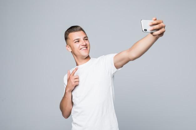 スマイリーの若い男は白いtシャツを着て、銀色のスマートフォンで自分撮りをしています。