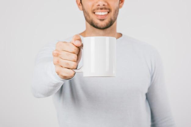 笑顔の若い男は、coffeマグカップを提供しています
