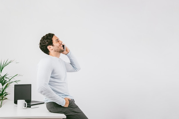 Smiley young man in the office talking on the phone