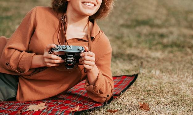 Смайлик молодая женщина держит камеру с копией пространства
