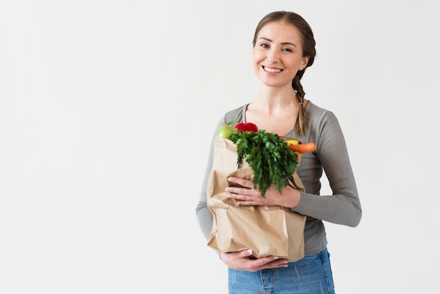 Smiley young woman holding paper bag with groceries