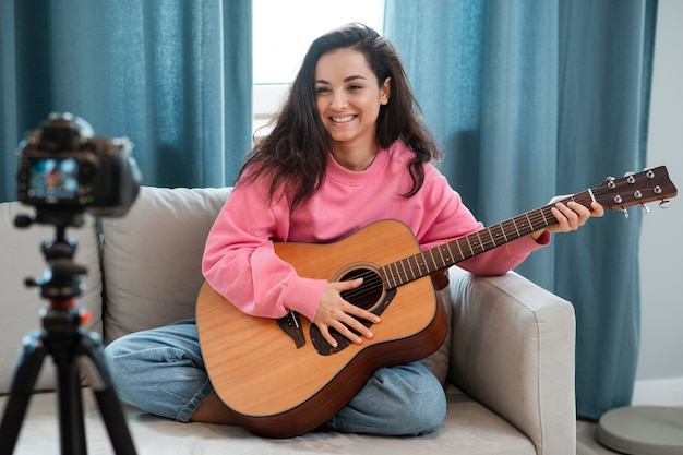 Smiley young woman playing guitar on camera