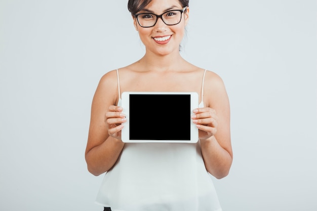 Smiley young woman presenting a tablet