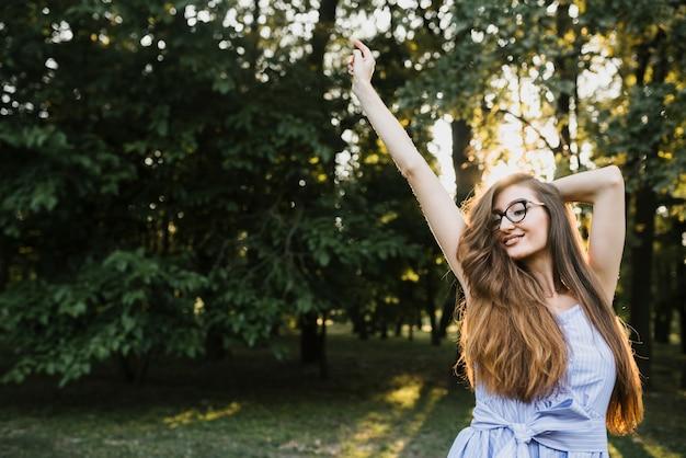 Смайлик молодая женщина, стоящая в солнечном свете