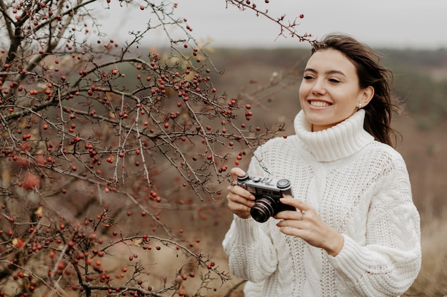Smiley young woman with camera