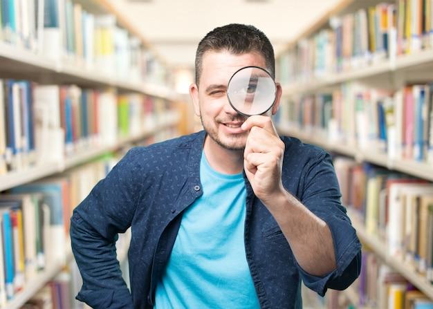 Молодой человек, одетый в синий наряд. с помощью увеличительного стекла. smili