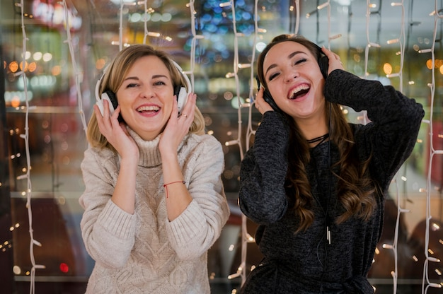 Smilig women wearing headphones near christmas lights