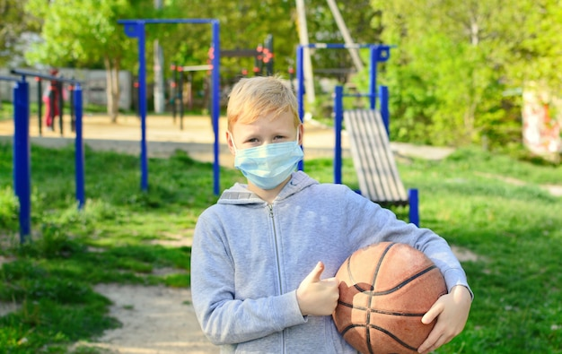 Улыбающийся 9-летний мальчик на улице снял медицинскую маску и играет в мяч. конец самоизоляции. коронавирус эпидемия.
