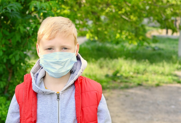 通りで微笑んでいる9歳の男の子は彼の医療マスクを脱いでボールをします。自己隔離の終わり。コロナウイルスエピデミック。