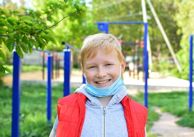 通りで微笑んでいる9歳の男の子は彼の医療マスクを脱いだ