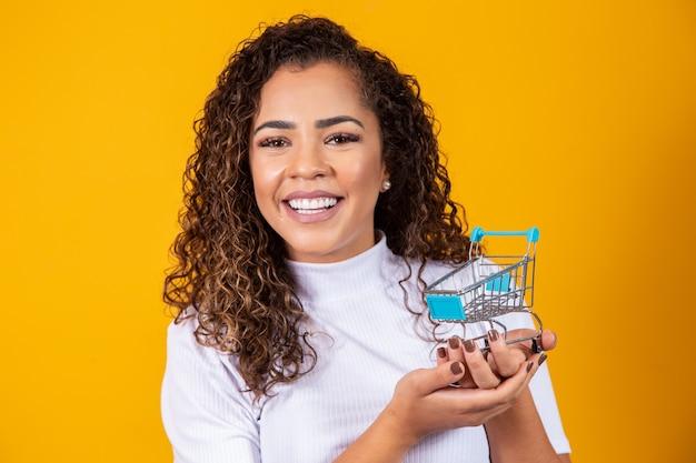 쇼핑 개념에서 웃는 곱슬 머리 여자. 미니어처 카트를 가진 젊은 여자. 전자 상거래 및 비즈니스. 쇼핑카. 여자 구매자입니다. 노란색 배경입니다.