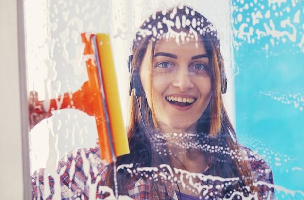 笑顔で、女性がブラシで窓を掃除します