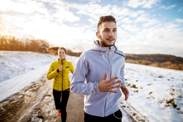 Улыбающийся активный человек в спортивной зимней одежде с наушниками и улыбающаяся девушка с хвостиком на улице в снегу